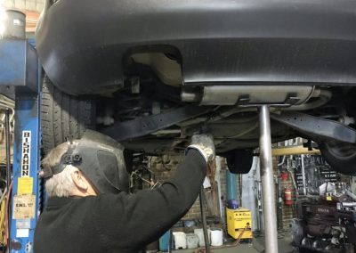 the fitting of a standard exhaust on a grey car
