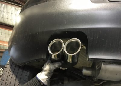 the result of fitting a new exhaust on a grey car