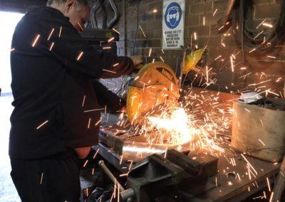 a worker grinding a truck exhaust