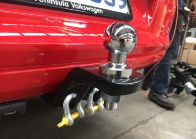 a new towbar fitted on a red Volkswagen